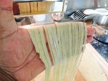 fresh-cut fettuccine through the pasta roller
