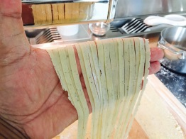 fresh-cut fettuccine through the pasta roller