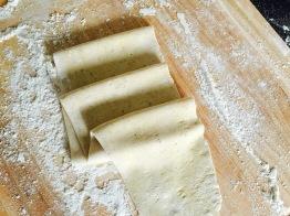 fresh pasta fed through pasta roller