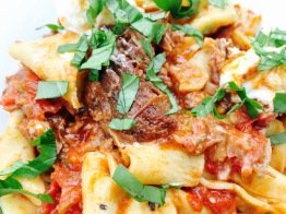 a serving of slow-braised beef pappardelle garnished with basil